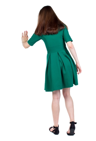 back view of woman. Rear view people collection. backside view of person. The slender brunette in a green short dress presses a button on the hand. Stock Photo