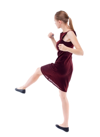 skinny woman funny fights waving his arms and legs. Isolated over white. girl in a burgundy dress has foot.