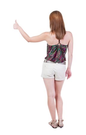 Back view of  woman thumbs up. Rear view people collection. backside view of person. Isolated over white background. slender blonde in a shorts shows the symbol of success or hitchhiking Stock Photo