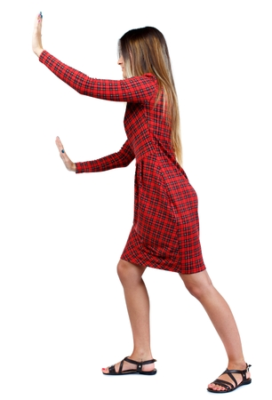 back view of woman pushes wall. girl in red plaid dress stands sideways and rests his hands on the wall. 版權商用圖片