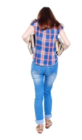 underarm: Girl comes with stack of books. back side view. Girl in plaid shirt holding out underarm textbooks. Stock Photo