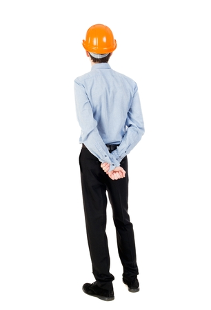 backview: Backview of an engineer in construction helmet stands. Curly businessman in a light jacket and a helmet with his hands behind his back and looking forward.