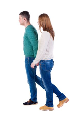 Back view going couple. walking friendly girl and guy holding hands. pair of warm sweaters goes right hand in hand. Stock Photo