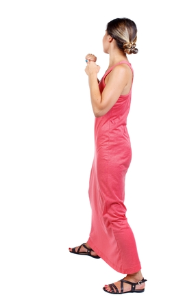 skinny woman funny fights waving his arms and legs. slender woman in a long red dress is standing with clenched fists. Stock Photo