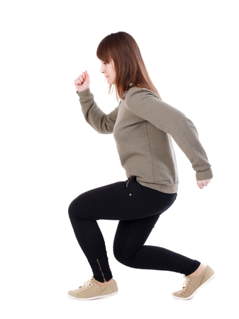 back view of standing young beautiful woman in jeans. backside view of person. Isolated over white background. A girl in a gray jacket goes on bent legs Stock Photo