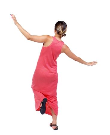 stumble: Balancing young woman. or dodge falling woman. slender woman in a long red dress balancing on his leg. Stock Photo