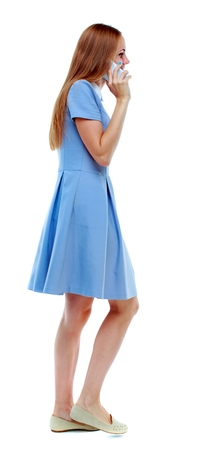 side view of a woman walking with a mobile phone. Isolated over white background. blonde in blue dress talking on the phone walking past.
