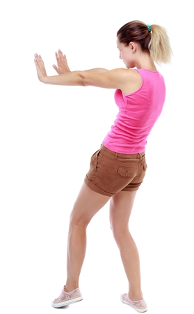 back view of woman pushes wall. backside view of person. Sport blond in brown shorts pushes away someone.