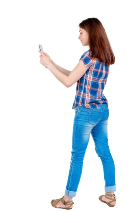 back view of standing young beautiful woman using a mobile phone. girl watching. Girl in plaid shirt standing sideways and photographs smartphone.