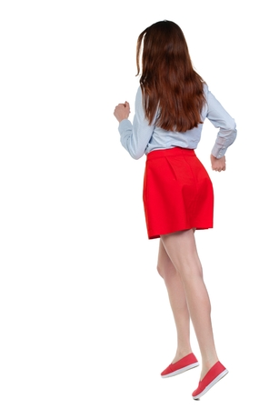 escapes: side view of running woman. beautiful girl in motion. Long-haired brunette in red skirt quickly escapes. Stock Photo