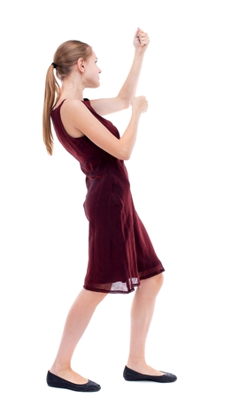 back view of standing girl pulling a rope from the top or cling to something. Isolated over white background. A girl in a burgundy dress hanging on a rope .. Stock Photo