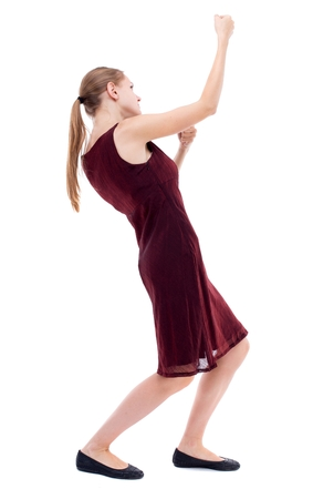 girl in burgundy dress: back view of standing girl pulling a rope from the top or cling to something. Isolated over white background. A girl in a burgundy dress pulls the load