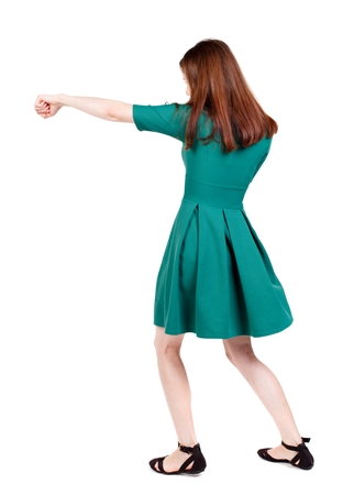 skinny woman funny fights waving his arms and legs. I The slender brunette in a green short dress has outstretched arm.