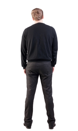 back view of Business man  looks ahead. Young guy in sweater watching.  Rear view people collection.  backside view of person.  Isolated over white background. office worker with his hands down looks ahead Stock Photo
