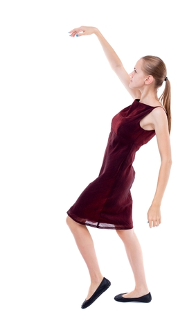 Balancing young woman. or dodge falling woman. Isolated over white background. A girl in a burgundy dress leans back.