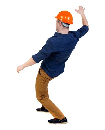 hombre cayendo: Equilibrio joven. o esquivar el hombre que cae. trasero vista de la persona. Aislado sobre fondo blanco. un hombre en un casco se echó hacia atrás con fuerza equilibradora.