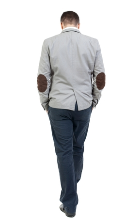 bowed head: Back view of walking businessman. bearded man in a gray coat walking with his hands in the pockets of his head bowed down.