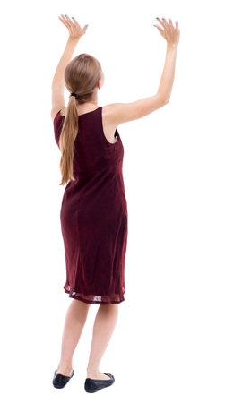 back view of woman protects hands from what is falling from above. Isolated over white background. A girl in a burgundy dress holding a load over your head. Stock Photo
