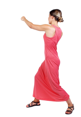 skinny woman funny fights waving his arms and legs. slender woman in a long red dress punches. Stock Photo