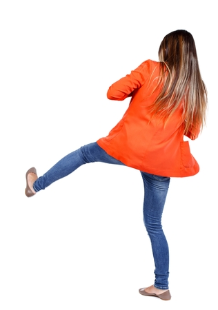 back view of woman funny fights waving his arms and legs. student in a red jacket kicks.