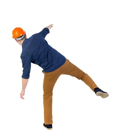 hombre cayendo: Equilibrio joven. o esquivar el hombre que cae. hombre con una camisa azul y un casco en equilibrio sobre la pierna derecha. Foto de archivo