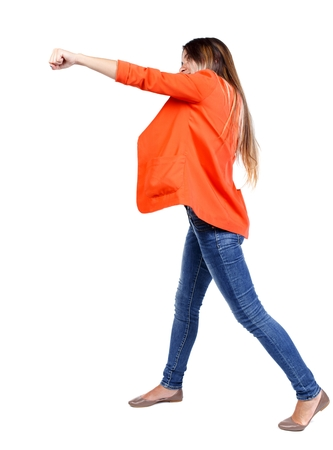 wimp: back view of woman funny fights waving his arms and legs. Rear view people collection. girl in a red jacket stands sideways and strike his hand.