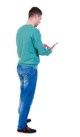 back view of business man uses mobile phone. man in a green jacket and jeans looking at tablet.
