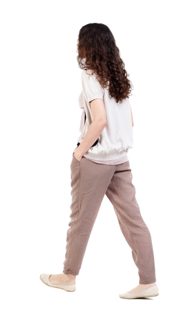 back view of walking curly woman. Long-haired curly girl walks slowly to the side with his hands in his pockets.