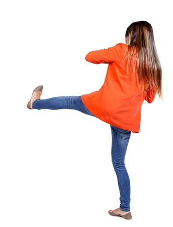 wimp: back view of woman funny fights waving his arms and legs. student in the red jacket has a foot. Stock Photo