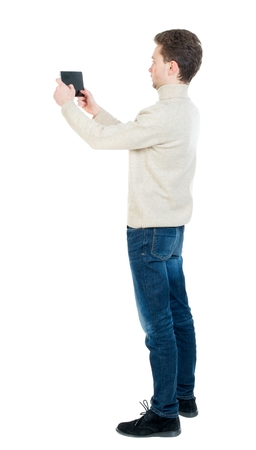back view of standing business man photographing a phone or tablet. Curly short-haired man in a woolen white jacket standing sideways and holding the tablet horizontally.