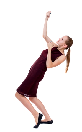 girl in burgundy dress: back view of standing girl pulling a rope from the top or cling to something. Isolated over white background. A girl in a burgundy dress pulls the top rope. Stock Photo