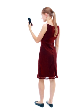 back view of standing young beautiful woman using a mobile phone. girl watching. Isolated over white background. The girl in the maroon sleeveless dress looks into the smartphone.