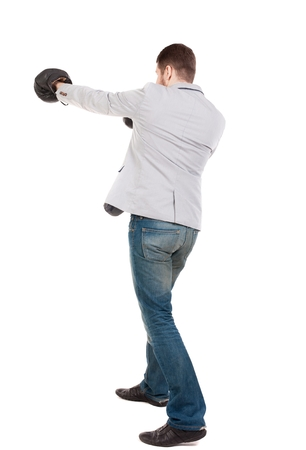 businessman with boxing gloves in fighting stance. guy in a gray jacket boxing gloves. Stock Photo