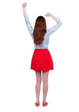 back view of dancing young beautiful woman. Long-haired brunette in red skirt lifted up his fists.