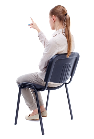 back view of young beautiful woman sitting on chair and pointing. Skinny girl in white denim suit sidit thoughtfully in his chair and points. Stock Photo