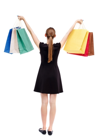 holding aloft: back view of woman with shopping bags. Isolated over white background. Blonde in a short black dress holding aloft shopping bags. Stock Photo