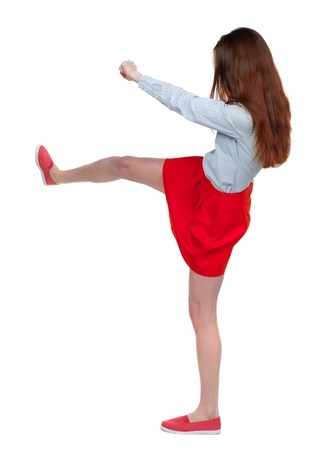 skinny woman funny fights waving his arms and legs. Long-haired brunette in red skirt is cancer and has foot.