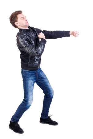 back view of guy funny fights waving his arms and legs. Curly guy in a black leather jacket clumsily fighting. Stock Photo