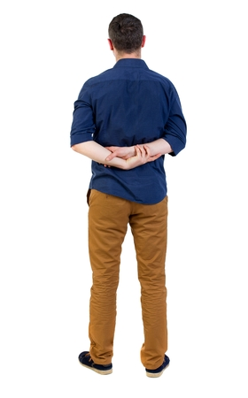 his shirt sleeves: Back view of man . Standing young guy. man in a blue shirt with the sleeves rolled up, standing with hands clasped behind his back.