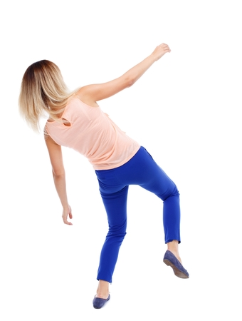 stumble: Balancing young woman. or dodge falling woman. Isolated over white background. The blonde in a pink shirt and slipped down. Stock Photo