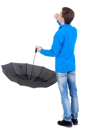 young man in in a white knit sweater under an umbrella. Curly boy in the blue jacket checks whether the rain ended. Stock Photo