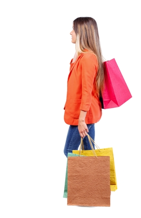side view of going woman with shopping bags . beautiful girl in motion. backside view of person. girl in red coat is throwing his bag on his shoulder.