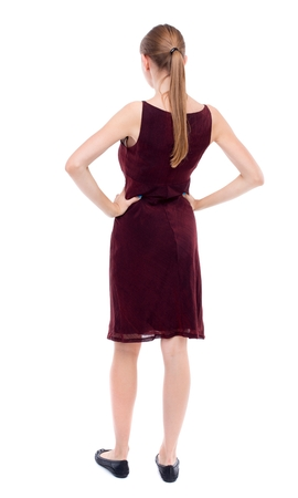 back view of standing young beautiful woman. girl in a burgundy dress sleeveless standing with hands on waist.