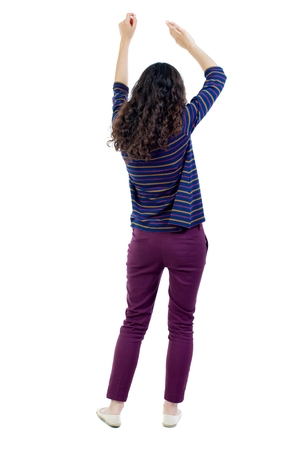 rejoices: back view of dancing young beautiful woman. Long-haired curly girl in a blue jacket rejoices Stock Photo