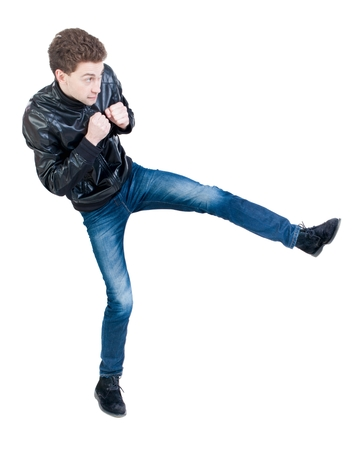 skinny guy funny fights waving his arms and legs. Isolated over white background. The boy timidly is kicked.