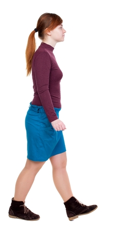 tied girl: back view of walking woman. Girl with red hair tied in a pigtail goes to the side. Stock Photo