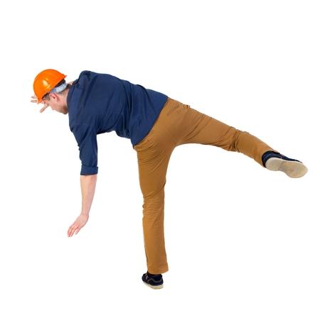 hombre cayendo: Equilibrio joven. o esquivar el hombre que cae. hombre con una camisa azul y un casco caídas tratando de mantener con el pie derecho. Foto de archivo