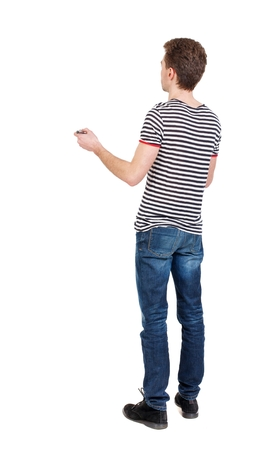 striped vest: back view of writing business man. Curly boy in a striped vest writes marker. Stock Photo
