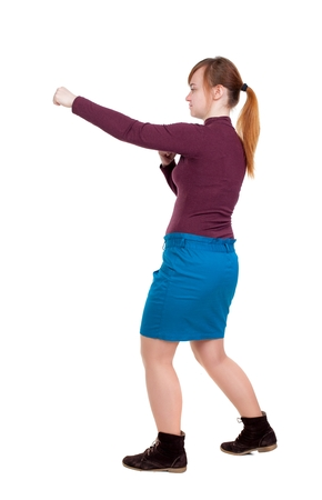 hair tied: skinny woman funny fights waving his arms and legs. Girl with red hair tied in a pigtail boxing.