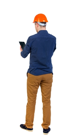 backview: Backview of business man in construction helmet stands and enjoys tablet or using a mobile phone. man in a blue shirt and a helmet stands with his back holding hands plashnet. Stock Photo